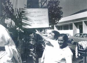 """Foto do casamento de Manoel Lopes Corrêa (""""Manezinho do Mocambo"""") e Hélia Lucas de Moraes, realizado sábado, dia 11 de julho de 1970, às 11horas, quando os amigos Benedito Nunes da Silva (""""Bodinho""""), já falecido, e Masahico Montsutsumi, faziam uma brincadeira afixando um cartaz convidando a população para a festa. Os dizeres do  cartaz: """"Seja bem-vindo nesta casa, traga chopp e churrasco, que lá dentro já tem brasa""""<br>"""