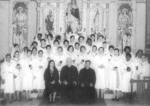 """Foto de 1950, de uma reunião das """"Filhas de Maria"""", grupo ligado à igreja católica. (1) Adelina Jabur Jamal, (2) Monsenhor João Rulli, (3) Padre Clemente. Em pé: (4) Maria Pereira de Souza, (5) Sônia dos Santos, (6) Amélia Fernandes, (7) Benedita Gonçalves, (8) Maria Eutália Colani Silva, (9) Maria Helena dos Santos, (10) Teresa Salvino, (11) Nair Contart, (12) Alice Fernandes, (13) Mariinha Lopes Correa, (14) não identificada, (15) não identificada, (16) Benedita, (17) não identificada, (18) Floripes Ferreira Barbosa Galdeano, (19) Maria Ferreira (""""Fiuca""""), (20) Germana Teixeira, (21) Almerinda Lopes Correa, (22) Teresa Lopes, (23) Maria Emília Lopes Correa, (24) Eunice Ferreira Barbosa, (25) Atuka Yokoyama, (26) Rosa Pereira de Souza, (27) Maria de Souza (""""Niquita""""), (28) Otília Silva, (29) Maria Couto, (30) não identificada, (31) Edna Conceição Ferreira Lopes, (32) não identificada, (33) Ivone Francisco dos Santos, (34) Maria da Consolação Ângelo Marini (""""Mariquita"""") , (35) não identificada e (36) Alcísia Barbosa."""
