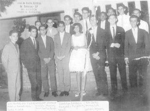 """Em 1961, reunião de jovens na Associação Atlética Ituveravense. Os trajes eram terno e gravata e vestido social, que na época eram muito usuais em festas e bailes. (1) Luiz Faleiros Nunes da Silva, (2) Antônio Márcio Ribeiro Sandoval, (3) João José Macedo Vilela, (4) Valter Abdalla Moisés, (5) Gláucia Cavalcante, (6) José Abdalla, (7) José Carlos Mirândola, (8) Artires Sandoval Henares, (9) Carlos Roberto Choff, (10) Walter Galdiano Gonzales, (11) Carlos Roberto Cardoso Telles, (12) José Carlos Borges, (13) Fernando Nogueira, (14) Antônio Sílvio Lopes, (15) Vagner José Bueno (""""Guitinho""""), (16) William Abdalla e (17) Arcênio Cadelca Filho"""