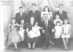 """Foto de 1948, da família Jacob Curi. (1) e (2) os patriarcas Abrão Jacob Curi e Faustina Abraão Curi, (3) José Jacob Curi, (4) Antônio Jacob Curi (""""Chanca""""), (5) Maria Jacob Curi (""""Merita""""), (6) Jorge Jacob Curi (""""Pracinha""""), (7) Therezinha Jacob Curi de Oliveira, (8) Marta Jacob Curi Ferrare, (9) Nadir Jacob Curi, (10) Lúcia Helena Curi Manfredini, (11) Karima Terezinha Jacob Curi dos Santos, (12) Valter Jacob Curi e (13) Cecília Jacob Curi de Pain"""