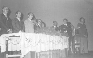 """Foto de 1971, da mesa que presidiu os trabalhos da solenidade de formatura dos alunos que concluíram do Curso Ginasial do Instituto de Educação """"Capitão Antônio Justino Faleiros"""". (1) o Delgado de Ensino José Rodini Luiz, (2) o prefeito Archibaldo Moreira Coimbra, (3) o diretor do Instituto de Educação, Octacílio de Paula Souza, (4) o patrono da turma, o militar da Reserva do Exército Brasileiro, José Olavo de Castro, (5) não identificado, (6) o promotor de Justiça, Hermenegildo Camargo Dias, (7) o vereador Ary Barbosa, (8) ao fundo, o professor Manoel Lázaro Pereira."""