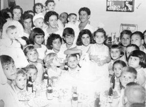 """Foto de 14 de agosto de 1958, do aniversário de Maria das Dores Alves Ferreira Azevedo (""""Dodô), na residência dos seus pais Eurico Alves Ferreira (""""Euriquinho da Farmácia"""") e Maria Ignês Bernardes Ferreira (ambos falecidos). Ela é casada com Carlos Alberto Inácio Azevedo e tem as filhas Vanessa Alves de Azevedo e Natália Alves de Azevedo. (1) a aniversariante Maria das Dores Alves Ferreira, (2) a mãe Maria Ignês Bernardes Ferreira, (3) o tio Miltom Alves Ferreira (in memoriam), com o filho Mário Alves Ferreira Neto, (4) José Miltom Alves (""""Tiquinho"""") (in memoriam), (5) Paulo Piratininga de Souza Vianna, (6) Cristina Nunes, (7) Lucélia Nunes, (8) Fátima Noêmia de Souza Vianna, (9) Regina Alves Ferreira, (10) e (11) Idalina de Oliveira Ferreira (in memoriam) e a filha Irene Alves Ferreira, (12) Túlio Del Guerra (in memorim), com a filha Margarete Germano Del Guerra e (13) Etelvina Falleiros"""