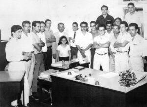 """Foto de 1965, de funcionários do Banco da Lavoura de Minas Gerais, onde hoje está instalado o Sicredi. (1) Antônio Ferreira de Matos, (2) Miguel Borges da Silveira (in memoriam), (3) Luciano José Duarte, (4) José de Freitas Macedo (""""Zito Macedo"""") (in memoriam), (5) Paulo José de Oliveira Neto, (6) e (7) o gerente Clodoaldo Salge (in memoriam) e a filha, (8) o inspetor do banco, (9) Justino Teodoro da Silva (in memoriam), (10) Alcino Alves Barbosa, (11) Edson Alves de Barros, (12) Aloísio Geraldo Godói, (13) Evandro de Paula Ferreira (in memoriam), (14) Eurípedes Pereira, (15) Antônio Salvador Cárdia, (16) Roberto de Melo (in memoriam), (17) Antônio da Silva (""""Toninho Saci"""") (in memoriam), (18) Alcides de Paula Teles (""""Tide"""")."""