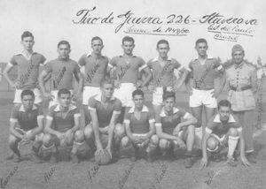 """Foto tirada em 7 de setembro de 1949, da equipe do Tiro de Guerra 226. (1) Devail Antônio Ciconeli, (2) Domingos Teoro (""""Chuin""""), (3) Wilson Cordaro, (4) Antônio Batista de Souza, (5) José Ferreira Filho (""""Escaretinha""""), (6) Jesus Rodrigues (""""Capucha""""), (7) o comandante do TG na época, sargento Hernani Peixoto, (8) Djalma Quadros Carneiro, (9) Rui Lacerda Diniz, (10) Fábio Bombig, (11) Horcalino Franco, (12) João Pugliani (""""Pavão"""") e (13) Nilo Chapini"""