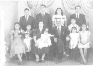 """Foto de 1948, da família Jacob Curi. (1) e (2) os patriarcas Abrão Jacob Curi e Faustina Abraão Curi, os filhos (3) José Jacob Curi, (4) Antônio Jacob Curi (""""Chanca""""), (5) Maria Jacob Curi (""""Merita""""), (6) Jorge Jacob Curi (""""Pracinha""""), (7) Therezinha Jacob Curi de Oliveira, (8) Marta Jacob Curi Ferrare, (9) Nadir Jacob Curi, (10) Lúcia Helena Curi Manfredini, (11) Karima Terezinha Jacob Curi dos Santos, (12) Valter Jacob Curi e (13) Cecília Jacob Curi de Pain"""