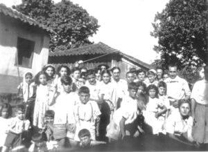 """Foto dos anos 40, de uma reunião de amigos e familiares na fazenda Santa Cornélia, de propriedade de Felipe Jorge. (1) Elza Jorge Pereira, (2) Mariana Germano, (3) Mera Jacob Liporaci, (4) Nagela Jugdar, (5) Lulia Jacob Alexandre, (6) Rolando Jugdar, (7) Alice Jugdar Moysés, (8) Meri Germano Mauad, (9) João Jacob Jorge (""""João Pitanga""""), (10) e (11) não identificados, (12) Jeorgete Abdalla Hanna, (13) Célia Jorge de Abreu Sampaio, (14) e (15) não identificados, (16) Elias Jorge (""""Lita""""), (17) José Jugdar, (18) Nadir Jacob Germano, (19) não identificado, (20) Evelin Jorge, (21) Milza Jorge Barbosa, (22) Reinaldo Jugdar, (23) Naime Jacob, (24) Antônio José Jacob (""""Toninho""""), (25) Mussi Jorge, (26) José Calin Germano, (28) Maurício Jugdar, (29) Zito Jugdar e (30) Jamil Jacob Germano"""