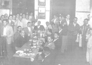 """Foto dos 40, de uma reunião de amigos no Bar Tupi, que era instalado no local em que um prédio frente ao Banco do Brasil, ode funciona x Yang. O proprietário era Paschoal Corona. (1) não identificado, (2) Wilson de Souza Vianna (""""Moringuinha""""), (3) Fábio Lacerda Diniz, (4) Mariano Giffoni, (5) Rubens França, (6) Francisco Alves Ferreira (""""Chiquinho da Farmácia""""), (7) Trajano Francisco Borges (""""Trajaninho""""), (8) Ayrton Gomes de Mello, (9) Edson Jabur, (10) Riode Raad (""""Marreta""""), (11) Esmeraldo Lino, (12) não identificado, (13) Alcides Mesquita Garcia, (14) Dirceu D'alkimim Telles, (15) Walter Mattar, (16) Archibaldo Moreira Coimbra, (17) Jorge Mattar, (18) Waibbe Germano, (19)Salim Moysés, (20) sobrinho do Riode Raad, (21) José Jabur (""""Zito""""), (22) Marcionílio Trajano Borges, (23) João Jorge Miguel (""""João Pitanga""""), (24) Osmar Chiconelli (""""Mazinho""""), (25) Zitinho Ferreira, (26) Roberto Telles, (27) João Máximo Borges (""""Zito Trajano""""), (28) o Dr. Nelson Soares de Oliveira,(29) Palmério Ramos e (30) O menino Luiz Henrique Corona, filho do proprietário do bar."""